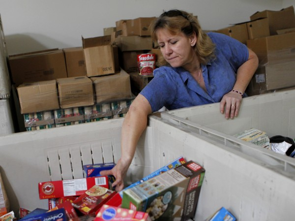 Office manager Chrissy Moe selects groceries for the emergency food supply pick-up. (Beth Schlanker / Press Democrat)