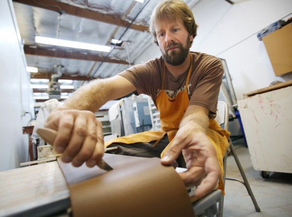 Ceramic artist Forrest Lesch-Middelton cuts pressed clay into square tiles at his studio in Petaluma. (Conner Jay / The Press Democrat)