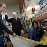 Customer Cynthia Putnam Leonard, left, is helped by store owner Gro Tomasini and sales assistant Cathy Cardoza as she selects fabric for a tablecloth.