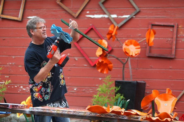 Pete Alexander assembles a flower he made at his studio in Penngrove. (Kent Porter / The Press Democrat)