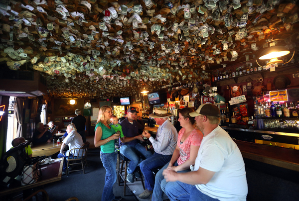 Thousands of faded business cards and dollar bills cover the ceiling of the Washoe House bar.
